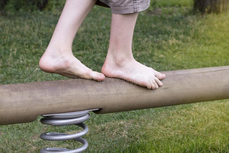 Os pés do ` s do menino vão em um feixe de equilíbrio infinito imagens de stock royalty free