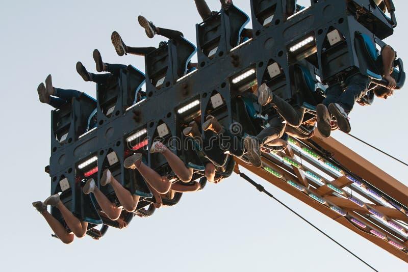 Os pés dos adolescentes oscilam no meio do ar no passeio da feira de condado fotos de stock