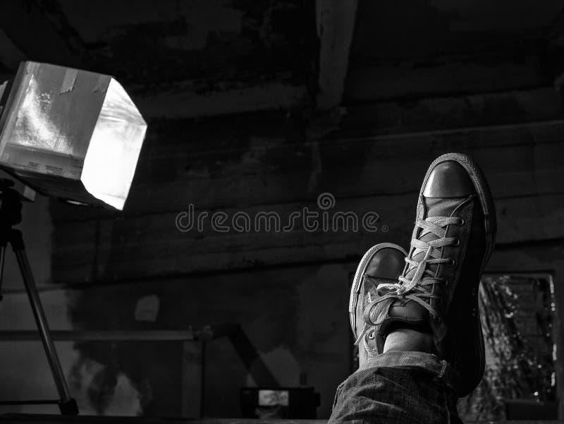 Os p?s dos homens nas sapatilhas aumentadas acima contra o teto Pequim, foto preto e branco de China imagens de stock