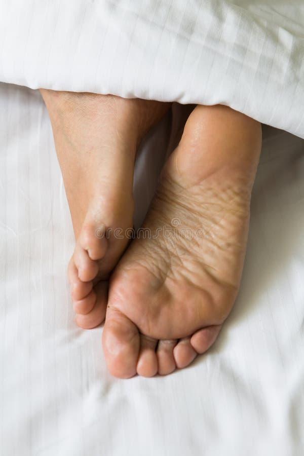 Os pés dos pés humanos projetam-se de debaixo da cobertura foto de stock