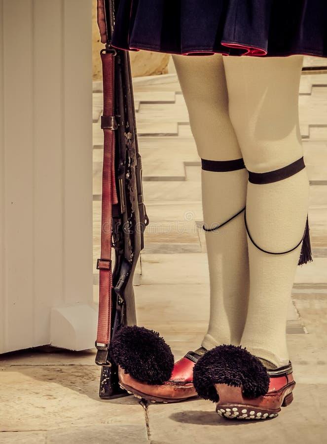 Os pés dos protetores gregos - Evzon - nas sapatas de madeira nacionais do Tsaruhi, levando o protetor na sepultura do desconheci imagens de stock royalty free