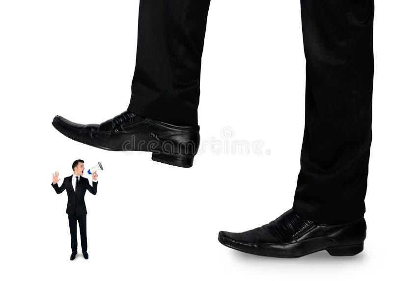 Os pés equipam o esmagamento de pouco homem de negócio foto de stock royalty free