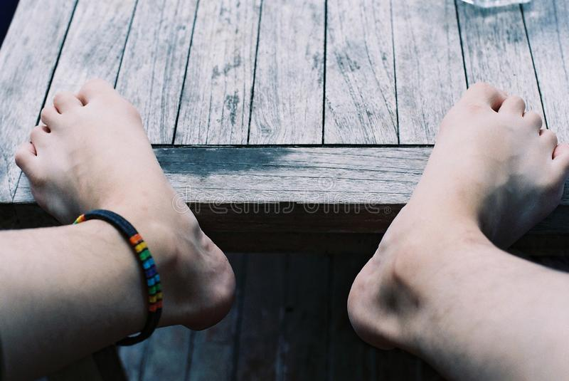 Os pés estão na tabela com o bracelete de tornozelo do arco-íris imagens de stock royalty free