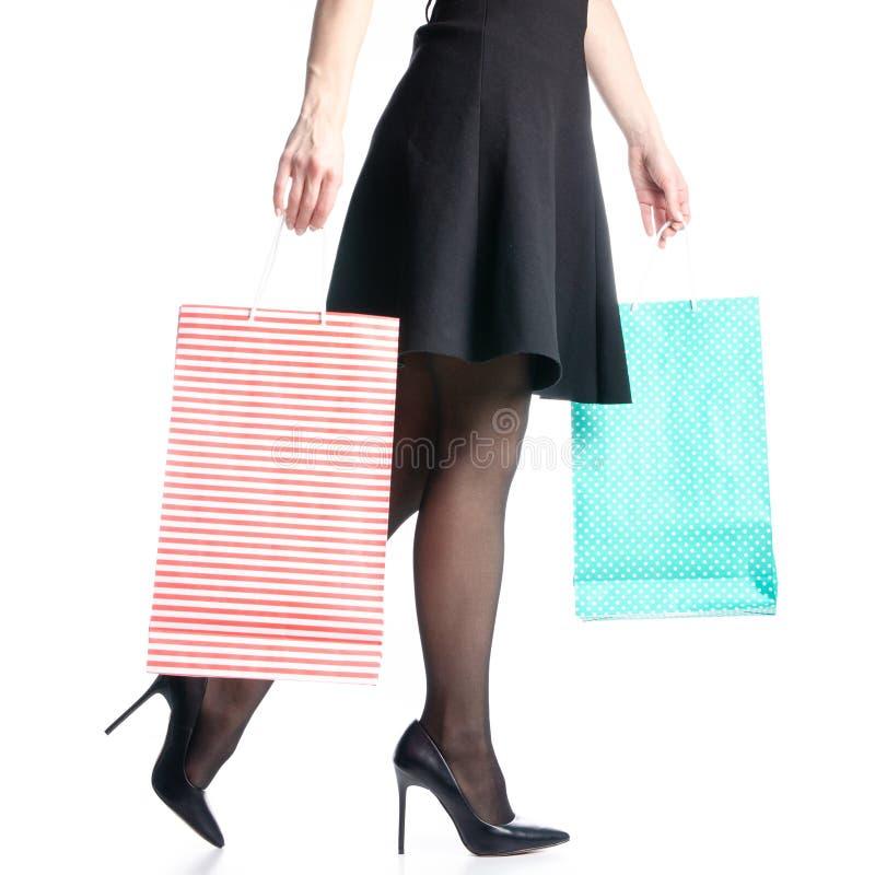 Os pés fêmeas em sacos pretos das sapatas dos saltos altos empacotam a forma preta da saia fotos de stock royalty free