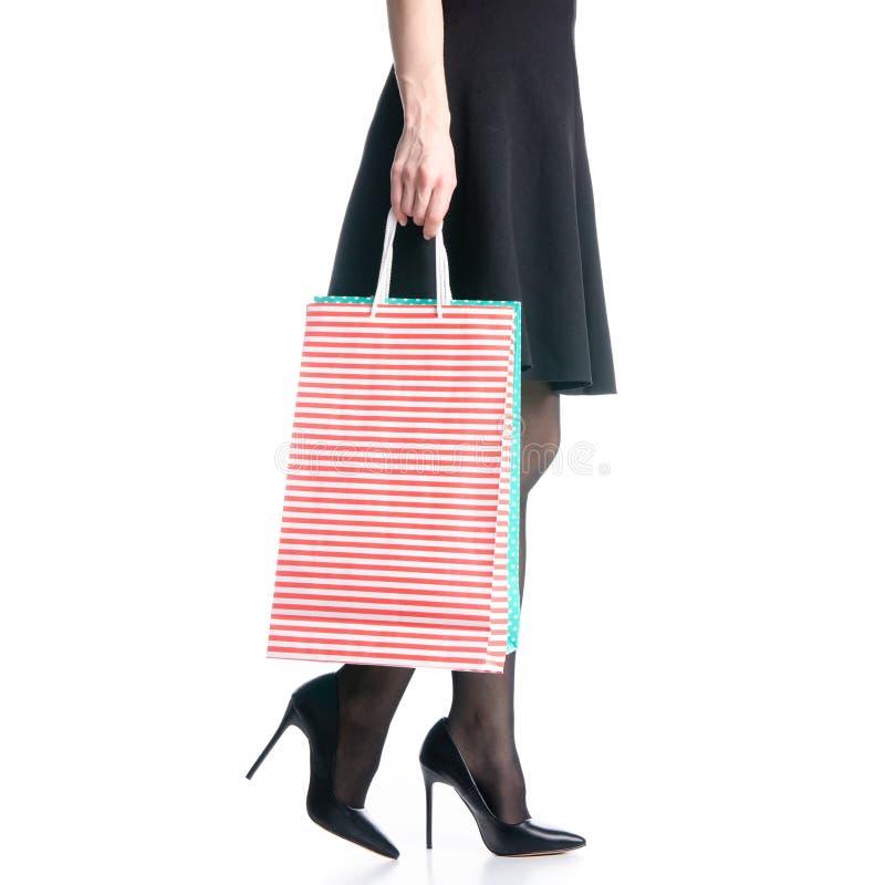 Os pés fêmeas em sacos pretos das sapatas dos saltos altos empacotam a forma preta da saia vão imagem de stock royalty free