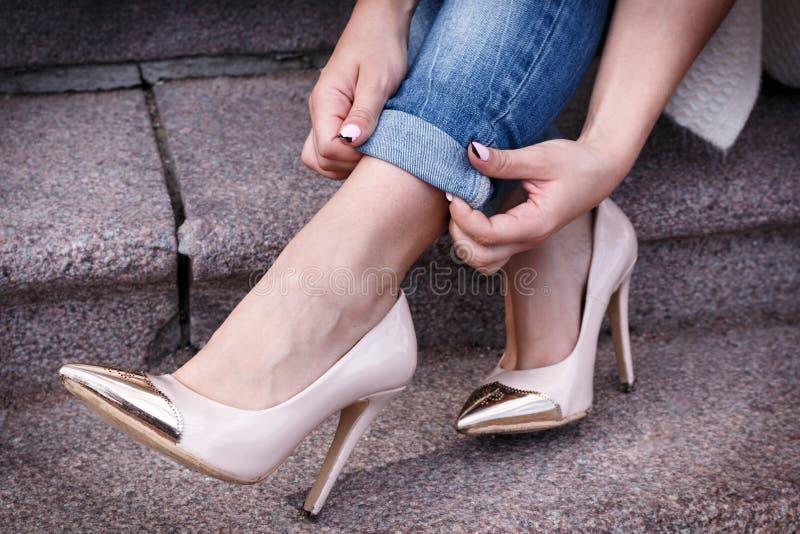 Os pés fêmeas em um pêssego bonito alto-colocaram saltos sapatas com nariz do ouro Close-up as mãos corrigiram calças de brim fotografia de stock royalty free