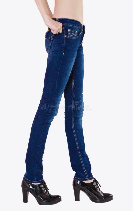 Os pés fêmeas esculturais vestiram-se na obscuridade - calças de ganga imagens de stock