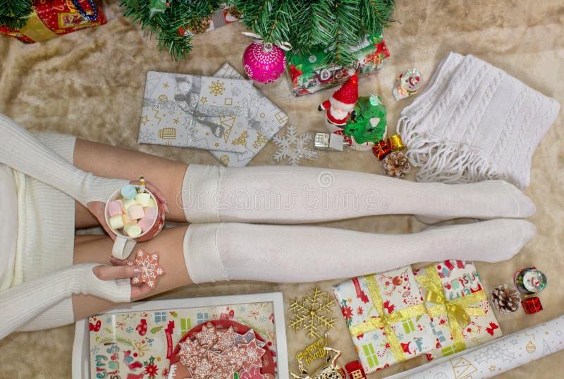 Os pés fêmeas, a menina estão guardando uma caneca de marshmallows Close-up Modo do Natal imagens de stock royalty free