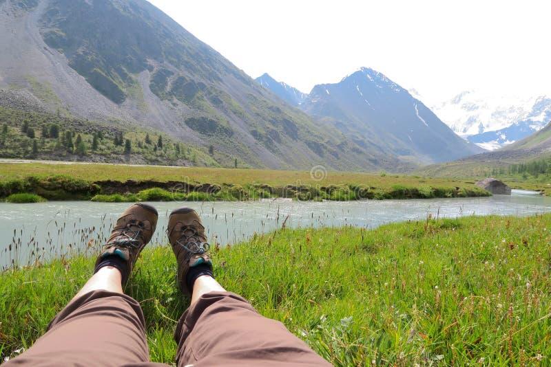 Os p?s f?meas na grama e nas montanhas ajardinam no fundo fotografia de stock royalty free