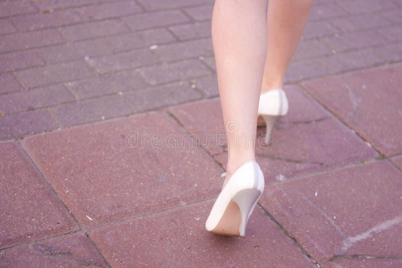 Os pés fêmeas no branco calçam os saltos altos Jovem mulher de piso Vista da parte traseira imagem de stock