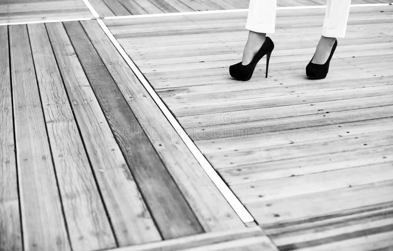 Os pés fêmeas no preto alto-colocaram saltos sapatas no assoalho das placas de madeira velhas imagens de stock