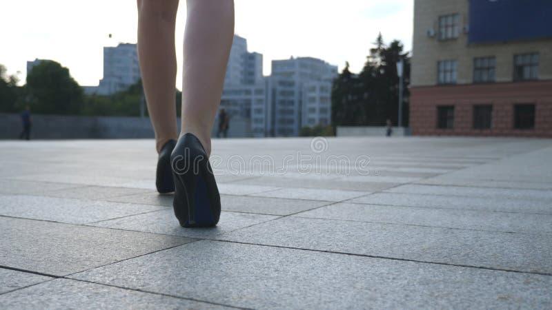Os pés fêmeas nos saltos altos calçam o passeio na rua urbana Pés da mulher de negócio nova em ir alto-colocado saltos dos calçad fotos de stock royalty free