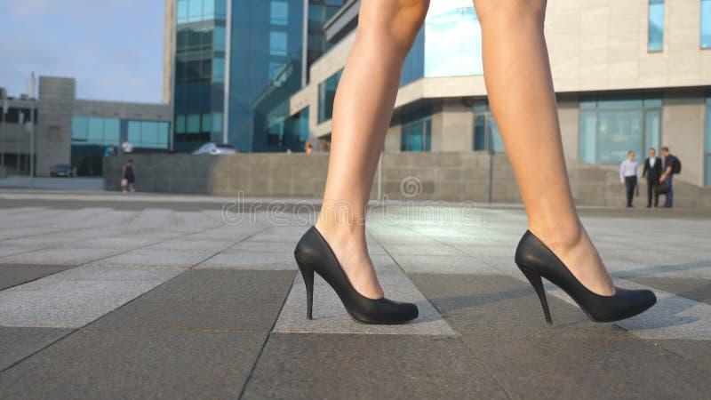 Os pés fêmeas nos saltos altos calçam o passeio na rua urbana Pés da mulher de negócio nova em ir alto-colocado saltos dos calçad fotos de stock