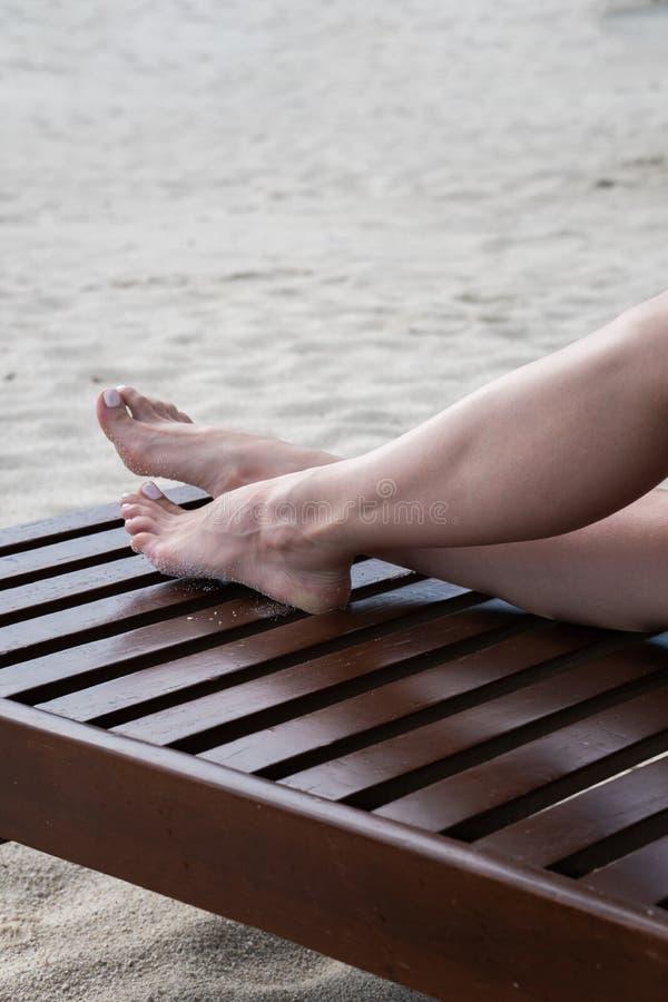 Os pés fêmeas tomam sol em um vadio Madeira escura da cor de Deckchair imagem de stock royalty free