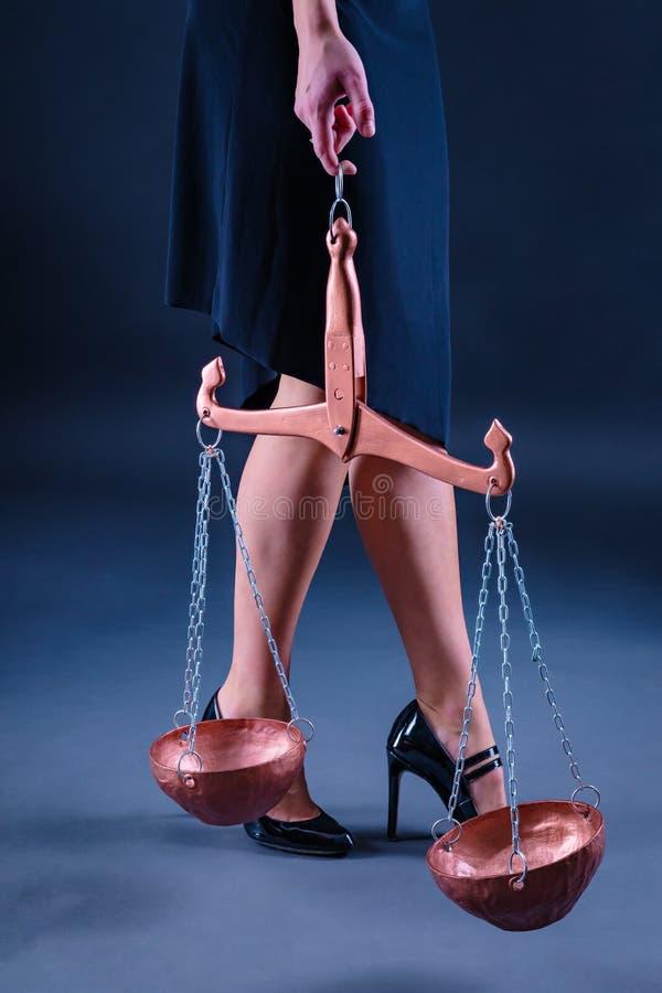 Os pés graciosos de uma moça e de sua Libra da terra arrendada da mão, como um símbolo do sinal do ar do zodíaco fotografia de stock