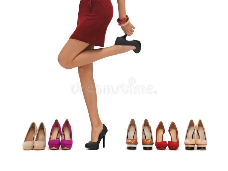 Os pés longos da mulher com saltos altos fotografia de stock