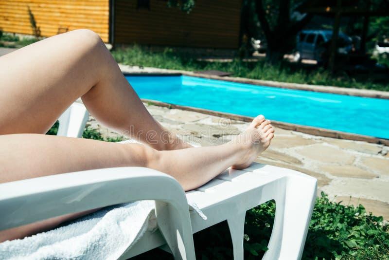 Os pés magros novos bonitos da mulher tomam sol perto da piscina foto de stock royalty free
