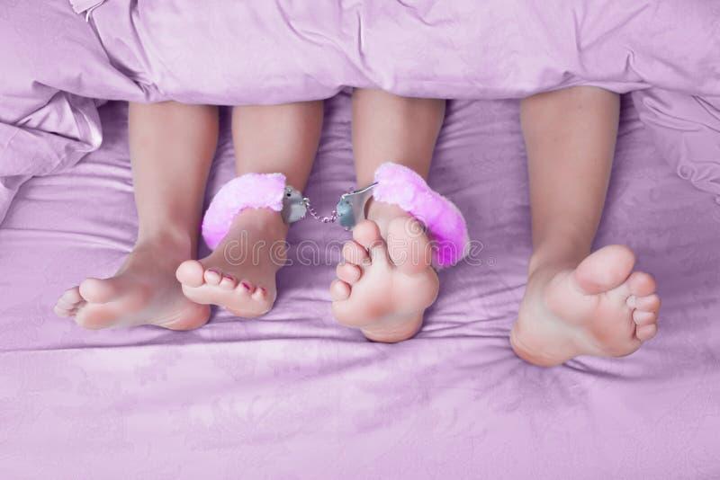 Os pés masculinos e fêmeas algemaram, brinquedo do sexo fotos de stock