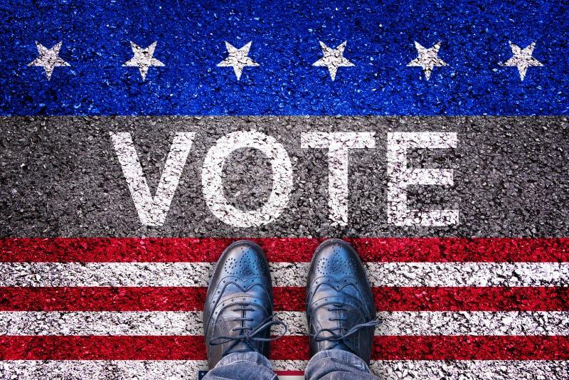 Os pés na estrada asfaltada com a palavra votam, conceito da eleição dos EUA imagens de stock