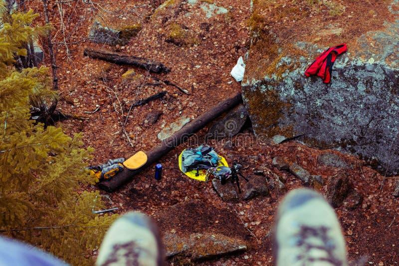 Os pés nas botas penduram de um penhasco alto que negligencia a opinião de primeira pessoa da floresta do outono foto de stock