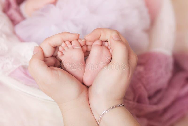 Os pés nas palmas, a mãe guardam os pés de sua criança recém-nascida em suas mãos fotos de stock royalty free
