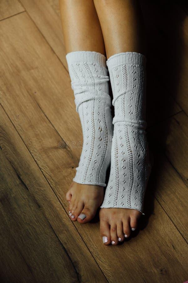 Os pés nas questiúnculas do dançarino de bailado sentam-se no assoalho no salão do estúdio gaiters unrecognizable foto de stock royalty free