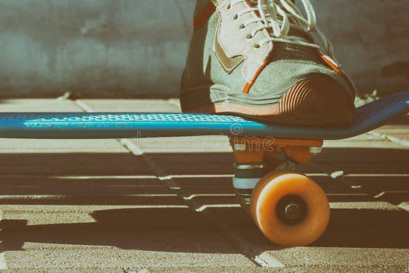 os pés nas sapatilhas do vintage estão em um skate Um skater está descansando em um banco no parque, uma tonificação artística do imagem de stock royalty free