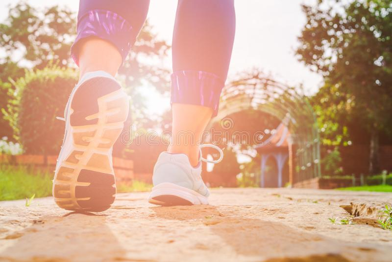 Os pés novos da mulher da aptidão que andam na manhã para aquecem o corpo para movimentar-se e o exercício no parque público exte fotografia de stock royalty free