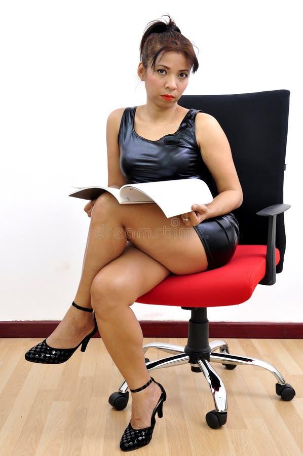 Os pés pretos 'sexy' do vestido da mulher cruzaram o documento aberto imagens de stock