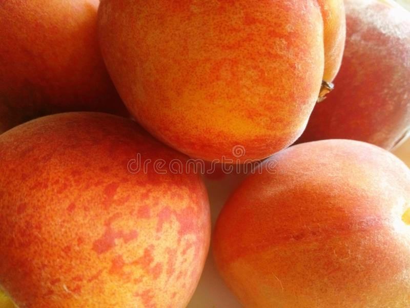 Os pêssegos estão na cor avermelhada cinco em número fotografia de stock