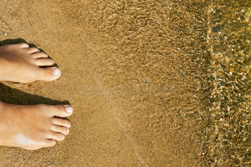 Os p?s desencapados da menina adolescente que est?o na areia de uma praia do lago perto da ?gua fotos de stock royalty free