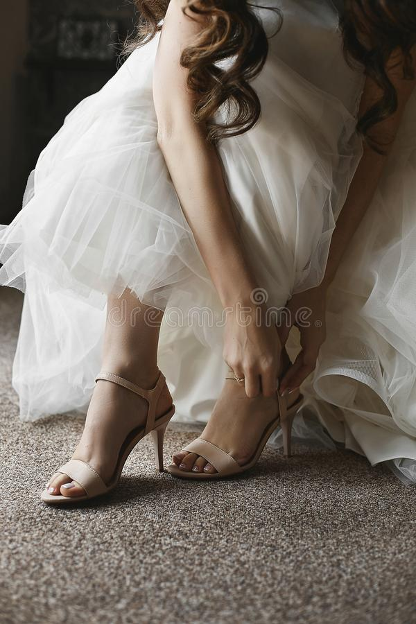 Os p?s f?meas bonitos em sapatas ? moda em um salto alto, a noiva p?em sobre sapatas do casamento sobre o salto alto fotos de stock