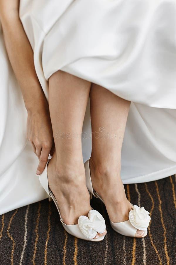 Os p?s f?meas bonitos em sapatas ? moda em um salto alto, a noiva p?em sobre sapatas do casamento sobre o salto alto imagem de stock royalty free