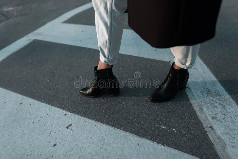Os p?s f?meas fecham-se acima A mulher em um revestimento longo nas botas pretas de couro em calças de brim à moda anda ao longo  fotografia de stock royalty free