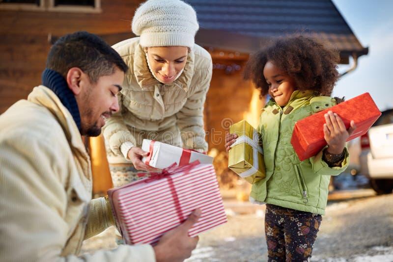 Os pais afro-americanos dão a sua filha pequena um Natal pre fotografia de stock royalty free