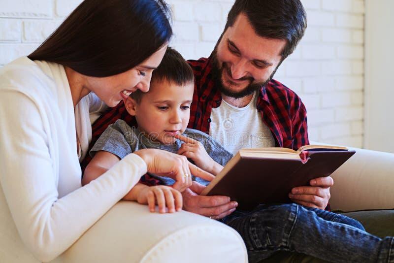 Os pais bonitos compartilham do tempo especial com a criança ao ler em fotografia de stock royalty free