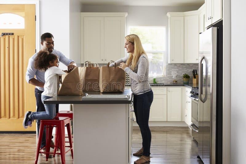 Os pais da menina e da raça misturada desembalam sacos de compras na cozinha imagens de stock royalty free