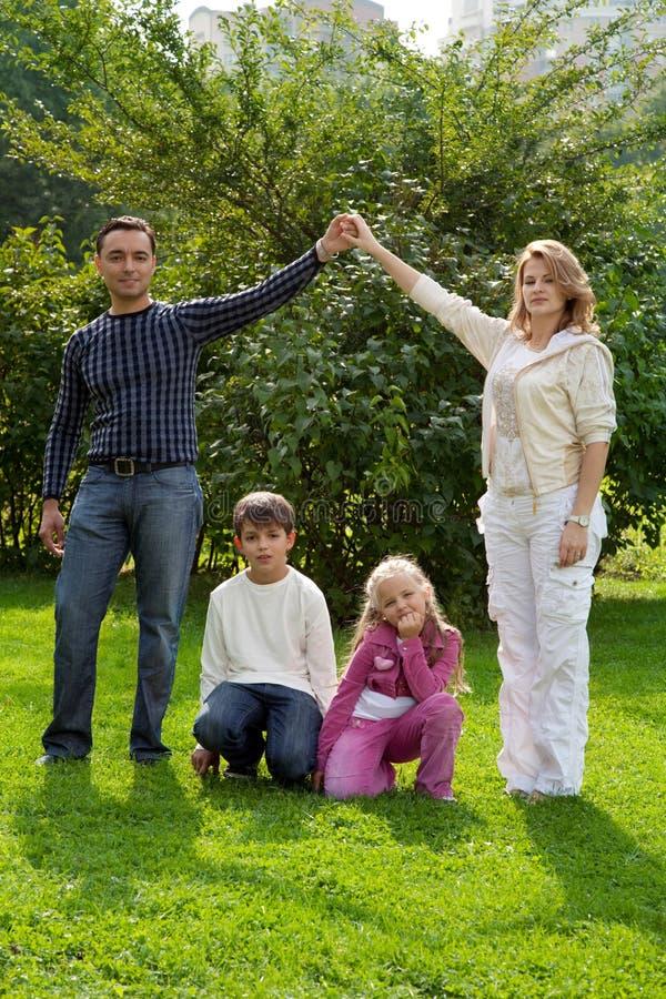 Os pais entregam à mão com crianças foto de stock
