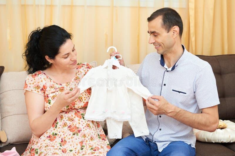 Os pais escolhem a roupa para o bebê recém-nascido Mulher gravida e homem Pares felizes que sentam-se no sofá em casa foto de stock royalty free