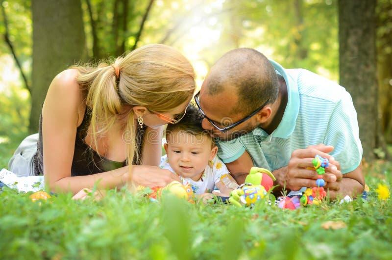 Os pais estão beijando seu filho imagens de stock royalty free
