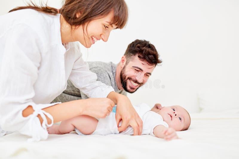Os pais fazem mudanças do tecido com seu bebê imagem de stock