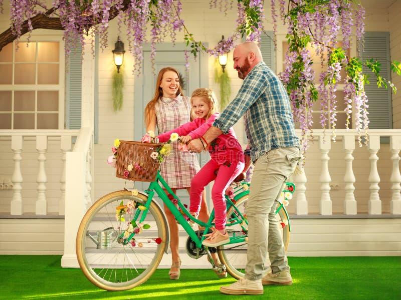 Os pais felizes com uma criança, filha, aprendem montar em casa uma bicicleta, férias de verão do estilo de vida da família fotografia de stock