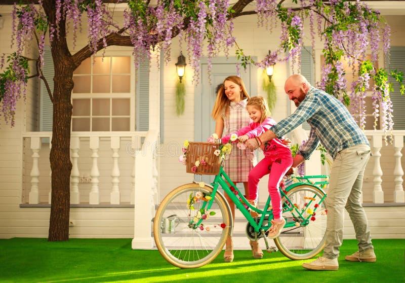 Os pais felizes com uma criança, filha, aprendem montar em casa uma bicicleta, férias de verão do estilo de vida da família fotos de stock royalty free