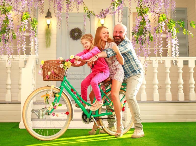 Os pais felizes com uma criança, filha, aprendem montar em casa uma bicicleta, férias de verão do estilo de vida da família imagens de stock royalty free