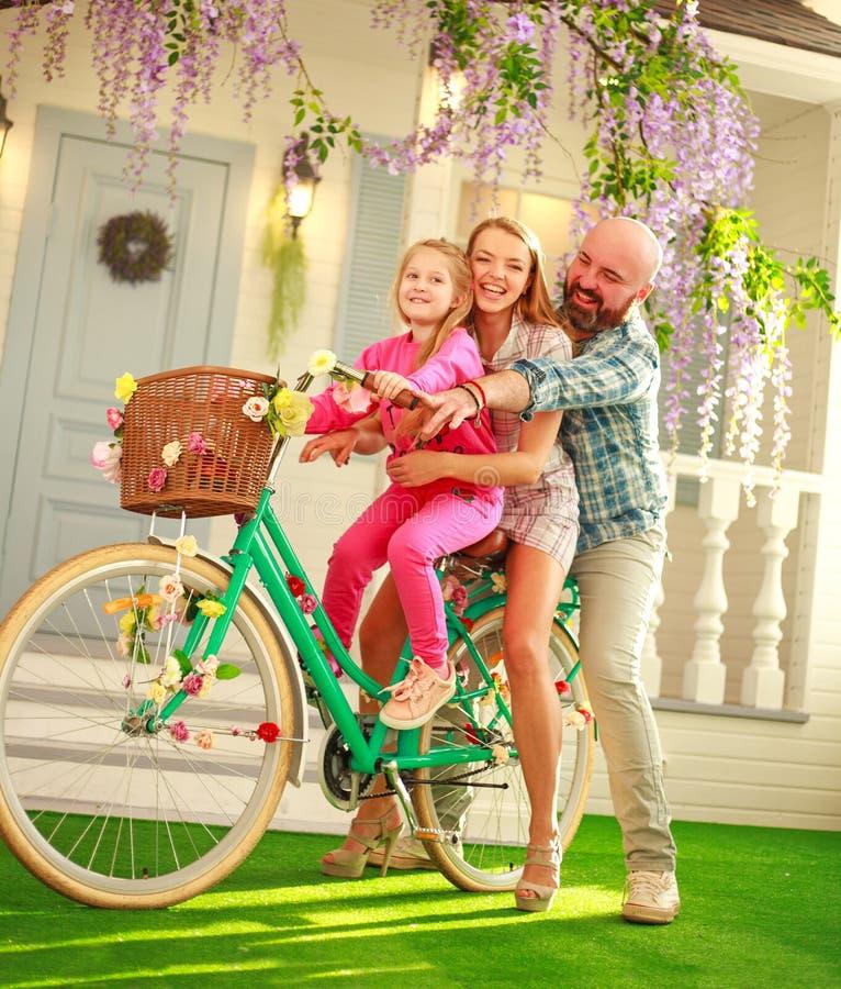 Os pais felizes com uma criança, filha, aprendem montar em casa uma bicicleta, férias de verão do estilo de vida da família imagens de stock