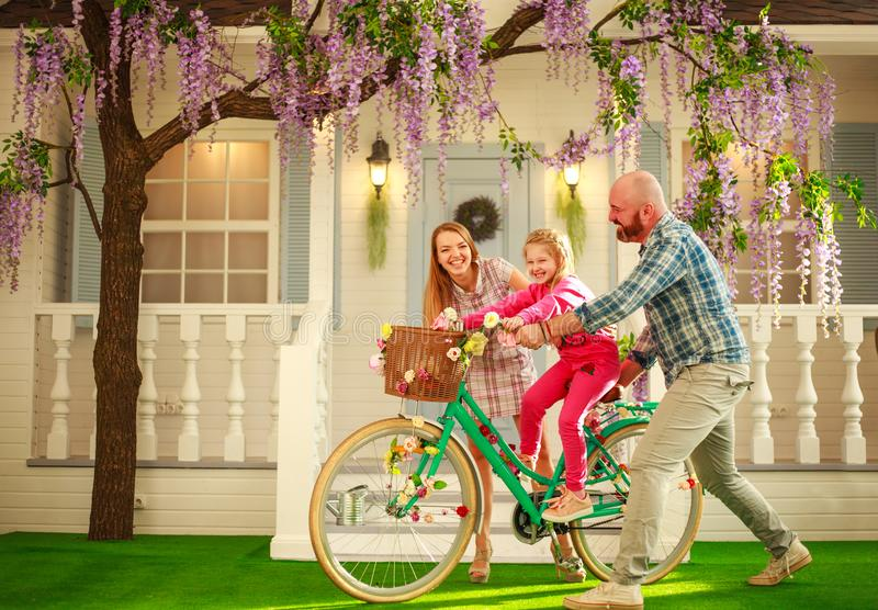 Os pais felizes com uma criança, filha, aprendem montar em casa uma bicicleta, férias de verão do estilo de vida da família fotos de stock