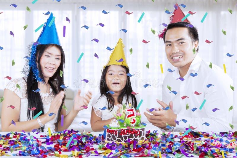 Os pais felizes comemoram o aniversário de sua filha fotos de stock