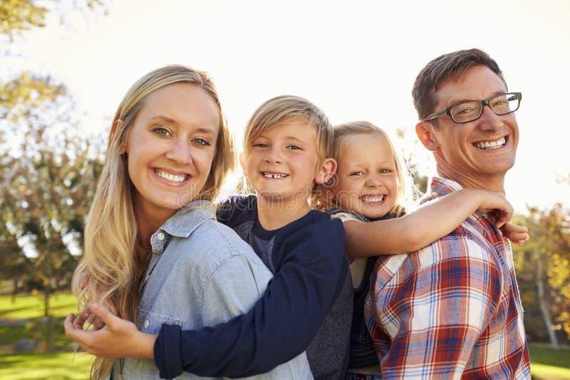 Os pais levam suas duas crianças rebocam em um parque, fim acima imagem de stock royalty free
