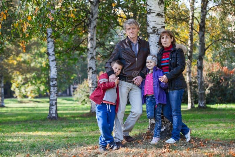 Os pais maduros com crianças estão junto no parque, comprimento completo imagem de stock royalty free