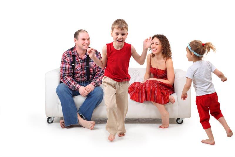 Os pais no sofá olham crianças running fotografia de stock royalty free